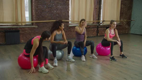 Positive Sporty Fit Women Resting on Fitballs at Gym
