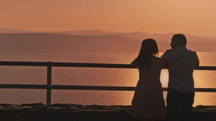Thumbnail for Young couple watching sunset above the lake from the viewing point. Medium shot.
