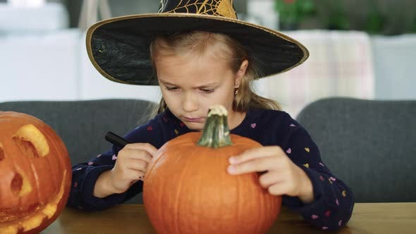 Thumbnail for Girl in halloween costume drawing on pumpkin