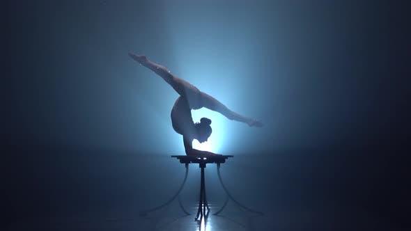 Акробат на столе показывает хитрости стоя на ее руках