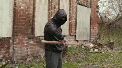Street Hooligan is Holding Twisting a Baseball Bat