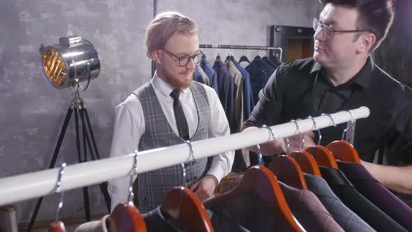 Thumbnail for Seller Helps a Young Man To Choose a Suit in the Store