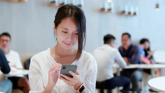 Thumbnail for Woman use of smart phone inside coffee shop