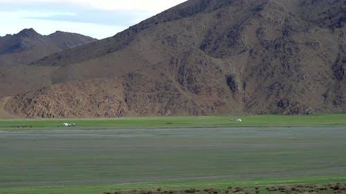 Mongolian Tents in Green Plain Beside The Treeless Hill