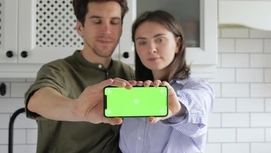 Man and woman are looking at the phone and showing on camera the mobile device Green screen