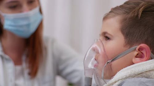 Boy with Symptoms of Dangerous Illness Uses an Inhaler To Prevent Lung Disease at Home on Bed with