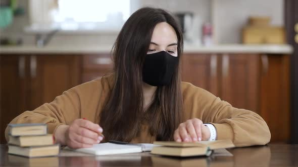 Girl in a Respiratory Mask Studying Distantly While Sitting at a Table