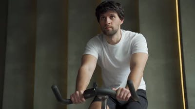 Muscular Man Which Using Bicycle in Gym