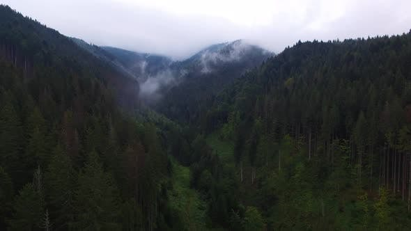 Aerial View. Flying over the high mountains in beautiful clouds. Aerial camera shot.
