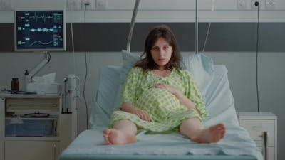 Portrait of Pregnant Person Sitting in Hospital Ward Bed
