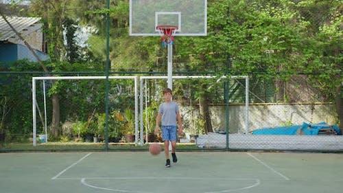 Junge übt Basketball im Freien spielen