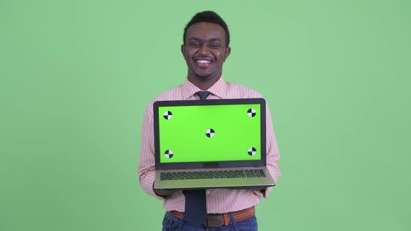 Thumbnail for Happy Young African Businessman Talking While Showing Laptop
