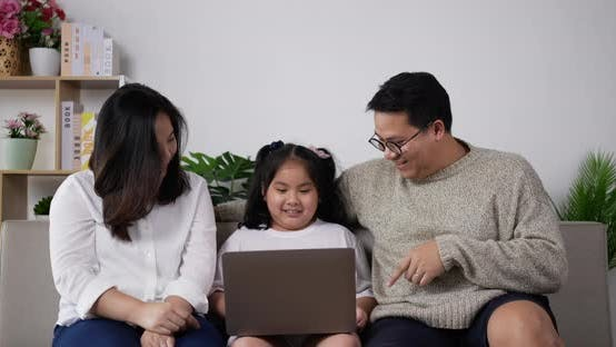 Young father and mother teaching lovely daughter use laptop computer
