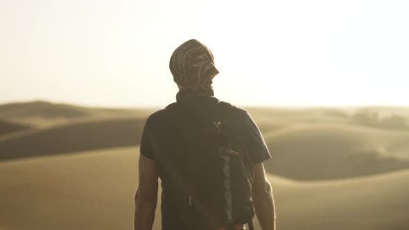 Thumbnail for Man Walking Through Sunlit Desert