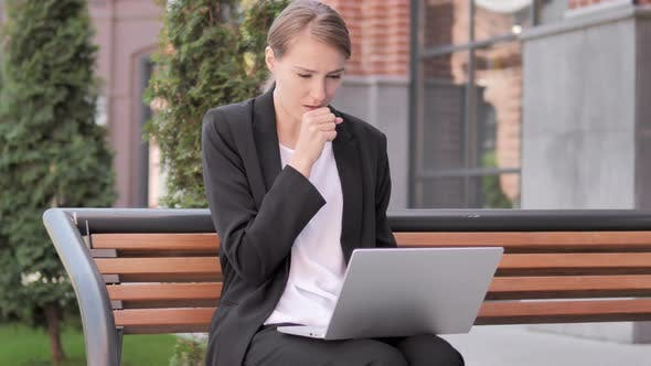 Cover Image for Young Businesswoman Coughing while Working on Laptop Outdoor