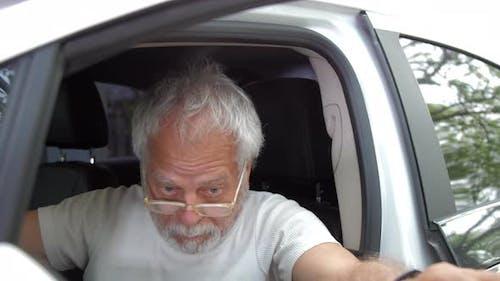 Inadequate Pensioner Man in Glasses Opens Automobile Door
