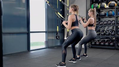 Beautiful Women Workout with Trx System in Gym