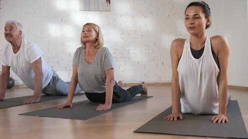 Yoga Teacher Doing Bhujangasana with Client Couple