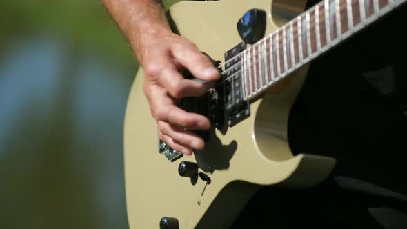 The young man plays the electric guitar  on the background of nature . close up.