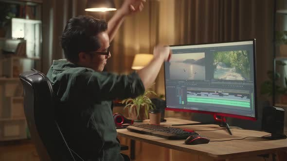 Asian Male Video Editor Stretching While Works With Footage And Sound On His Personal Computer