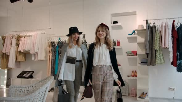 Happy Female Shoppers with Shopping Bags Leaving Fashion Store