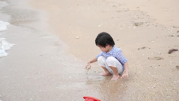 Cute Asian Child Playing On The Beach