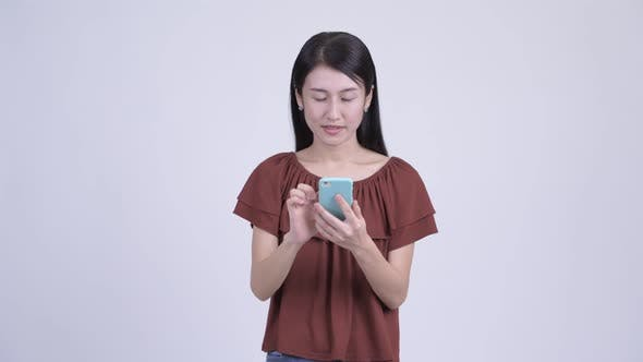 Cover Image for Happy Beautiful Asian Woman Using Phone and Looking Surprised