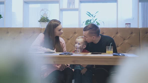 Thumbnail for father and kid look at mom and talk sitting in restaurant