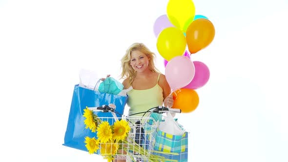 Thumbnail for Woman on bike with balloons and shopping bags