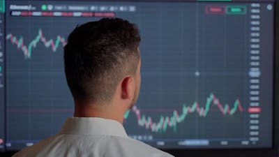 Man trader looking at graph currency money at screen indoors. Male businessman person check money