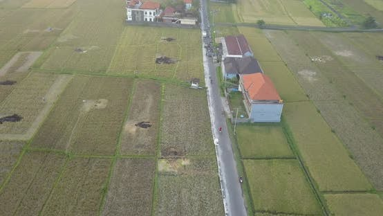 Aerial drone view of a man riding his motocross motorcycle on a road in Bali.