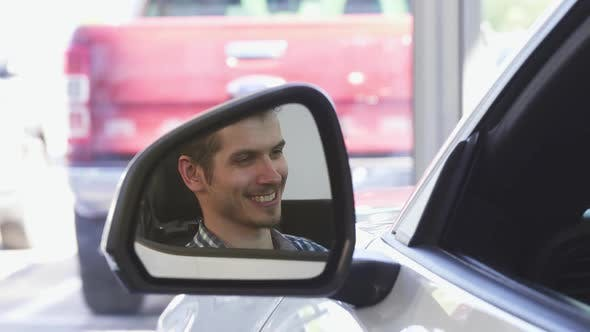 Thumbnail for Happy Male Driver Smiling in the Side Mirror of a Car