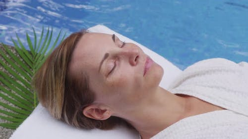 Woman at spa lays by pool. Shot on RED EPIC for high quality 4K, UHD, Ultra HD resolution.
