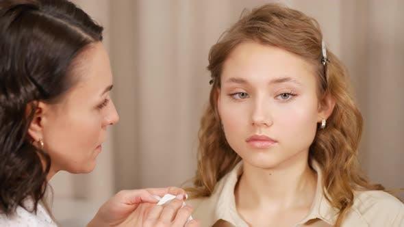 Thumbnail for Makeup Master stellt Make-up auf das Gesicht des Kunden. Anwenden von Farbe auf die Lippen des Mädchens.