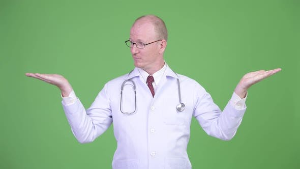 Thumbnail for Mature Bald Man Doctor Comparing Something