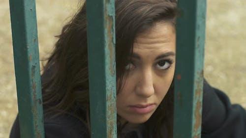 Gefangenschaft, Depression, Traurigkeit - Junge Frau hinter Gittern