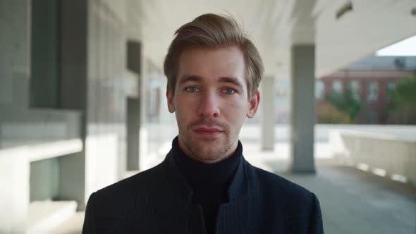 Porträt eines gutaussehenden ernsthaften Mannes, der vor einem städtischen Hintergrund in die Kamera bli