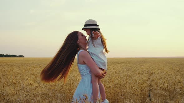 Slow Motion Mom with Daughter Spinning in Field