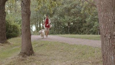 Caucasian Man Walking Dog in Park