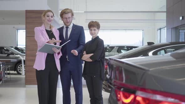 Thumbnail for Car Saleswoman Shows a Young Couple Information About Luxury Car in Showroom