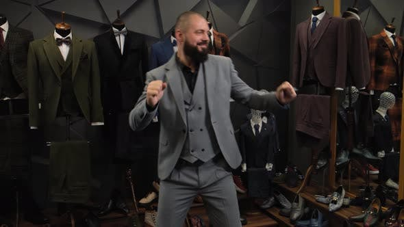 Thumbnail for Happy and Confident Man Dancing in a Taoilor Shop. Millennial Businessman with Classic Suit Perform