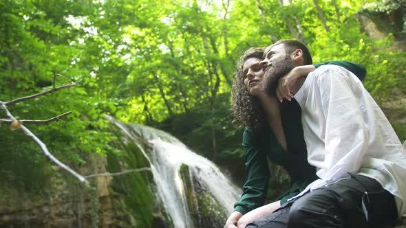 Thumbnail for Young Couple - Man with Beard and Woman with Curly Hair Is Hugging and Kissing By Sitting on Stone