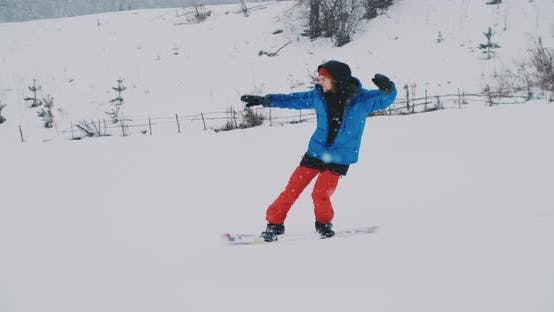 Thumbnail for Male Snowboarder Rides on a Board in the Snow From the Ski Slope