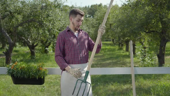 Funny Young Bearded Farmer Fooling Around, Imitating Playing Guitar Using the Pitchfork