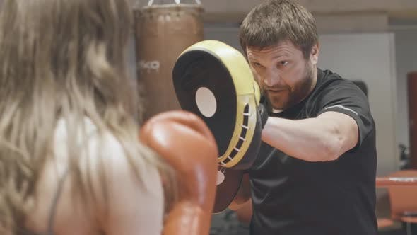Brunette Caucasian Coach in Training Gloves Working with Female Boxer on Boxing Ring. Confident