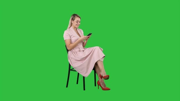 Cover Image for Thoughtful woman in pink dress texting on smart phone on