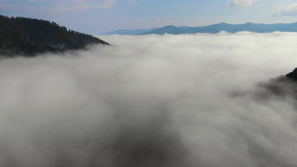 Aerial drone shot of amazing dense fog above river between mountains.