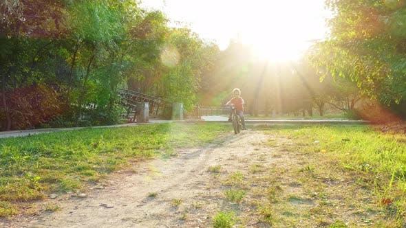 Boy Kicks Off and Rides a Bike