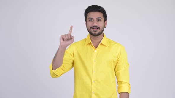 Thumbnail for Young Happy Bearded Indian Businessman Pointing Up