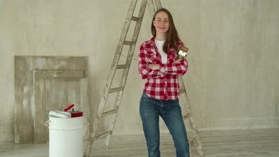 Woman Paints Walls at Home Holds Paint Brush
